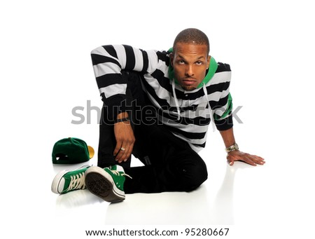 Portrait of African American hip hop man sitting isolated over white background