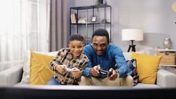 Portrait of African American joyful young male parent having fun with small son sitting on sofa in apartment and playing video games on console in good mood. family time, playtime, gamer concept
