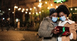Portrait of African American loving husband wearing medical mask on street and giving xmas gift to his wife on new year's eve. Joyful woman feeling surprised and happy getting present Holidays concept