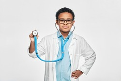 Portrait of African American male kid wearing a doctor coat with phonendoscope, standing on light grey background