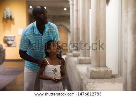 Portrait of African American man and his daughter at hall of Art Museum among exhibits of antiquity