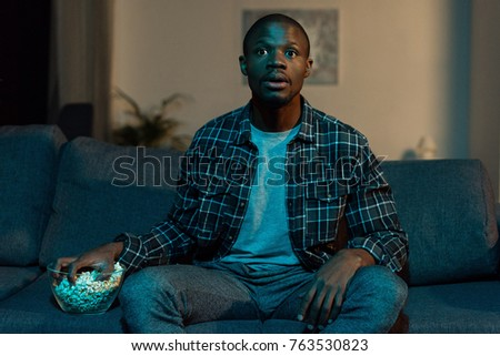 portrait of african american man with popcorn watching tv at home
