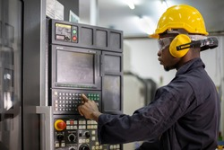 Portrait of African American mechanic engineer worker wearing safety equipment beside the automatic lathe machine in manufacturing factory