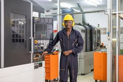 Portrait of African American mechanic engineer worker wearing safety equipment beside the automatic lathe machine in the manufacturing factory