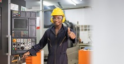 Portrait of African American mechanic engineer worker wearing safety equipment showing thumbs up beside the automatic lathe machine in manufacturing factory with copy space
