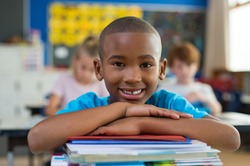 Portrait of african american schoolboy leaning on desk with classmates in background. Happy young kid sitting and leaning chin on stacked books. Portrait of elementary pupil looking at camera.