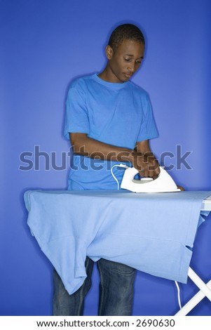 Portrait of African-American  teen boy ironing shirt standing against blue background.