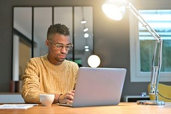 Portrait of african american trendy guy working from home on laptop