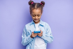portrait of african child girl with mobile phone in hands, isolated over purple background. sweet child chatting with friend or watching something interesting on phone