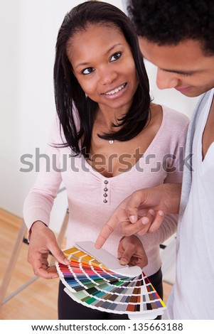 Portrait Of African Couple Choosing Color For New Home