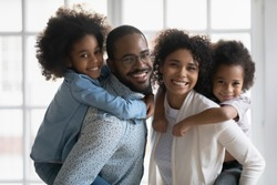 Portrait of African ethnicity parents piggy back son and daughter posing indoors. Pretty family looking at camera photo shoot in modern apartment at home, happy parenthood family services ad concept