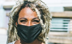 Portrait of african girl with blond dreadlocks wearing face protective mask for Coronavirus prevention - Covid 19 lifestyle and trendy people concept - Focus on face