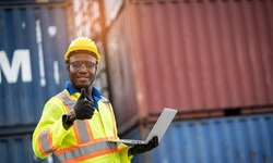 Portrait of African happy worker in safety jumpsuit work wear with hardhat and use laptop computer at cargo container shipping warehouse. transportation import,export logistic industrial