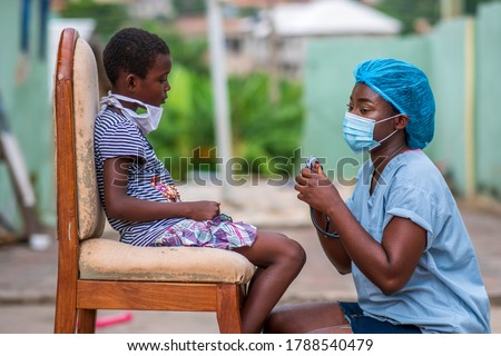 portrait of African health worker wearing surgical face mask and attending to a child patient also wearing a homemade mask for protection in covid-19 pandemic season-concept on child healthcare