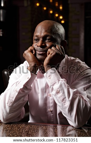 Portrait of african man in pink shirt sitting at desk leaning on fists