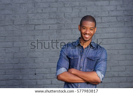 Portrait of African man smiling against gray wall with blue shirt #577983817