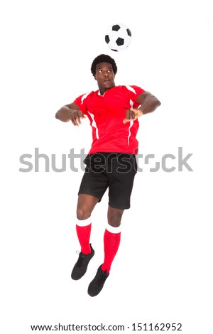 Portrait Of African Soccer Player Playing With Football Over White Background