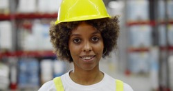 Portrait of african woman worker in safety hardhat standing in warehouse. Young black female manager wearing protective uniform smiling at camera in storehouse