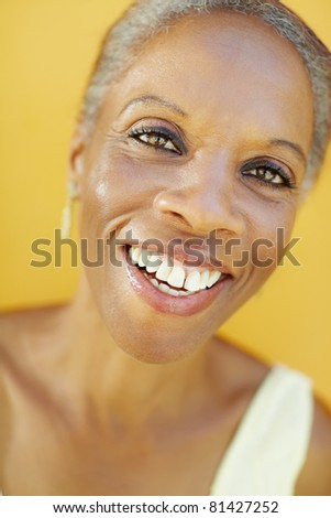 portrait of african 50 years old surprised woman with white hair, smiling on yellow background