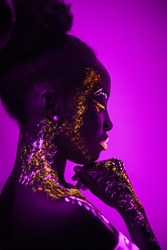 Portrait of african young woman with fluorescent makeup on face and skin that glowing in ultraviolet light. colorful, interesting and unusual shoot. side view. pink background