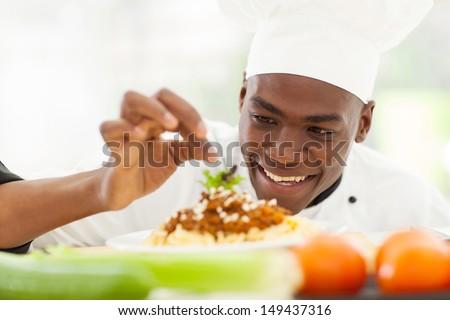 portrait of Afro American chef in restaurant kitchen garnishing pasta dish