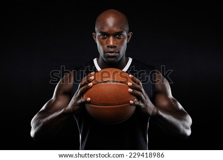 Portrait of afro american male basketball player with a ball over black background. Fit young man in sportswear holding basketball.