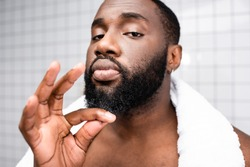 portrait of afro-american man using cure for strengthening beard growth