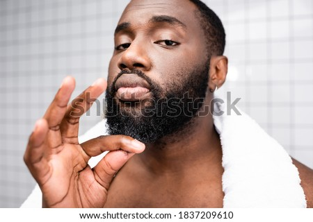 portrait of afro-american man using cure for strengthening beard growth Stock photo ©