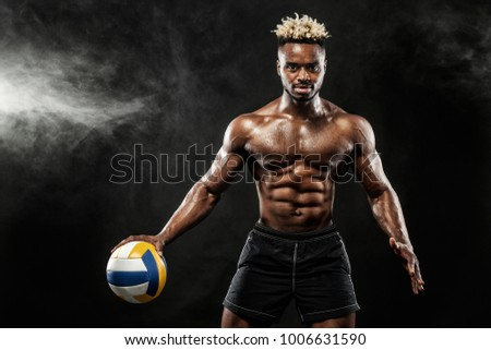 Portrait of afro-american sportsman, valleyball player with a ball over black background. Fit young man in sportswear holding ball.