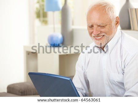 Portrait of aged man at home looking at laptop computer screen, smiling.