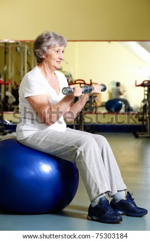 Portrait of aged woman doing physical exercise with barbells while sitting on blue ball