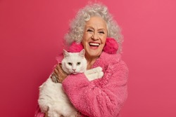 Portrait of aged wrinkled woman enjoys good day with favorite white cat, wears domestic robe, feels not bored on retirement, going to feed pet, loves animals, poses indoor against pink background
