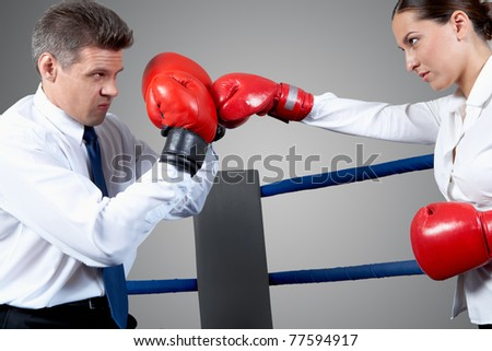 Portrait of aggressive businessman in boxing gloves fighting with serious female opposite him