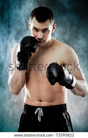 Portrait of agressive male boxer with splashes of water on background