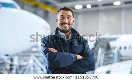 Portrait of Aircraft Maintenance Mechanic in Hangar. Airplane on Background.