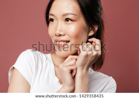 Portrait of alluring asian woman dressed in basic wear smiling and looking aside isolated over red background in studio Foto d'archivio ©