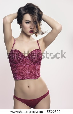 portrait of alluring girl with brown hair and cute make-up wearing red sexy underwear in sensual pose