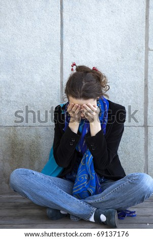 Portrait of alone young urban girl sitting at dirty wall look like  grunge background