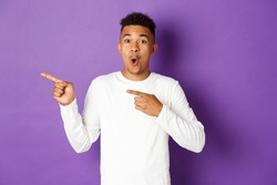 Portrait of amazed african-american man in white sweatshirt, looking impressed and showing advertisement, pointing fingers left, standing over purple background