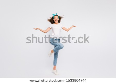 Portrait of amazed astonished girl in blue headband feel crazy enjoy wind her hair blowing flying hold hands scream wow omg wear t-shirt denim jeans sneakers isolated over white color background