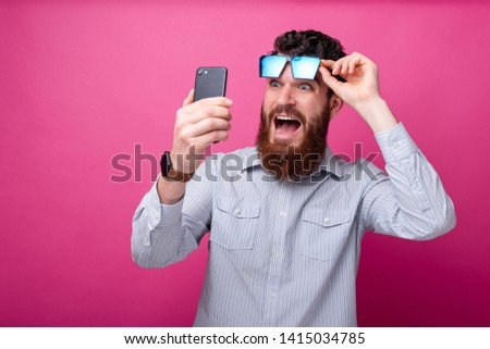 Portrait of amazed bearded man looking shocked at smartphone and standing over pink background
