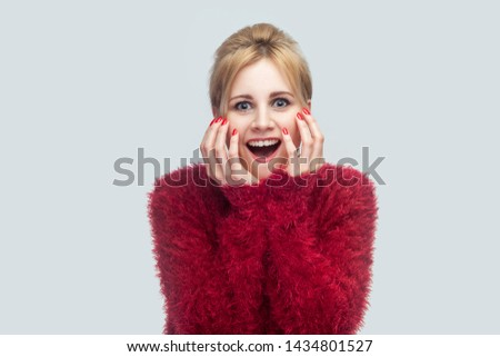Portrait of amazed beautiful young blond woman in red blouse standing and looking at camera with surprised face and happiness news touching face. indoor studio shot isolated on light gray background.