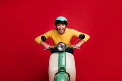 Portrait of amazed cheerful funky crazy girl addicted moped scooter rider drive bike enjoy speed scream wow omg wear jumper isolated over vivid color background