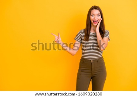 Portrait of amazed crazy girl promoter point index finger copy space recommend way promotion adverts wear modern clothing isolated over bright color background