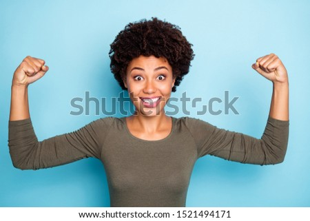 Portrait of amazed crazy girl show muscles impressed by her power scream wow omg wear casual style clothes isolated over blue color background