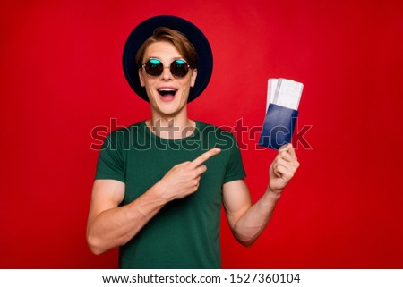 Portrait of amazed excited brunette hair tourism lover guy travel on weekends hold tickets point index finger scream wow omg wear blue headwear green t-shirt isolated over red color background