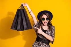 Portrait of amazed excited girl shopping center client point index finger bags she buy store ear retro style outfit headwear isolated over bright shine color background