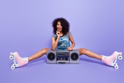 Portrait of amazed excited girl sitting with boom box planning theme party on roller skates enjoying hip hop music listening favorite song isolated on bright violent background