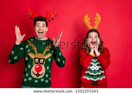 Portrait of amazed excited two people family wife husband brunet hair scream wow omg hear  news  wear season christmas tree hipster pattern pullover sweater isolated over red color background
