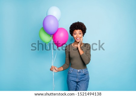 Portrait of amazed funky afro american girl hold colorful baloons receieved for her anniversary present from friends scream wow omg wear good look outfit denim jeans isolated blue color background
